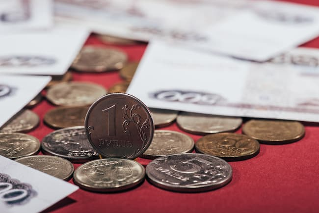 Money spread onto a red table.